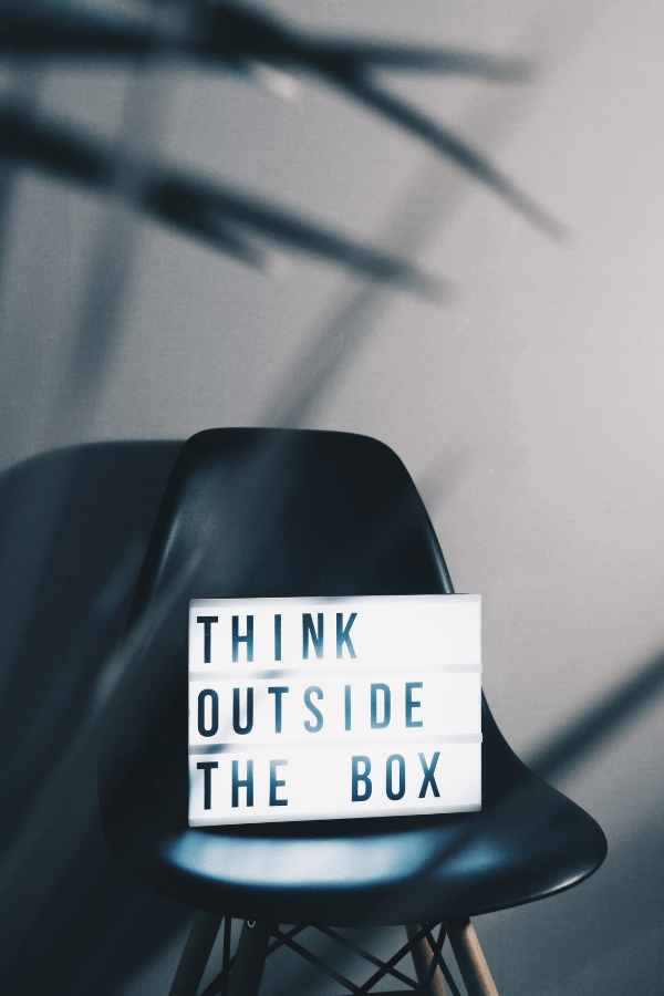 Think Outside The Box sign on a black chair.